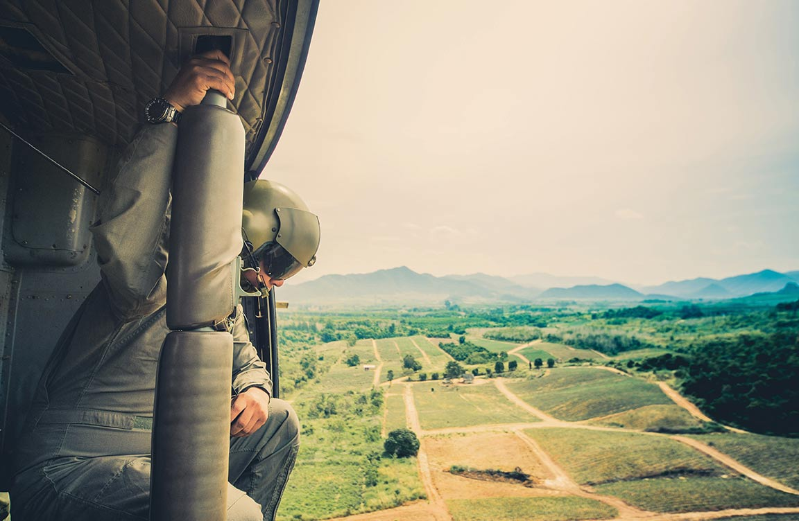 Man in a helmet looking out over fields and mountains.