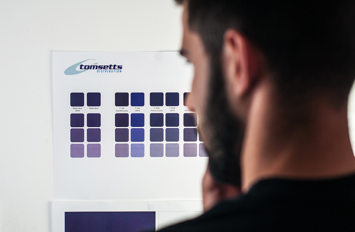 Bearded man looking at a colour chart on the wall.