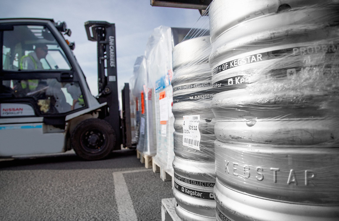 A truck lifting up some boxes, with kegs in the foreground.