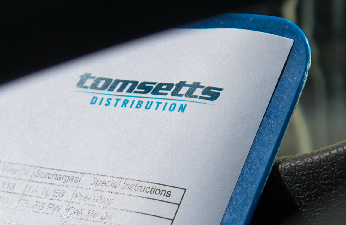 The Tomsetts logo on a page on a clipboard.